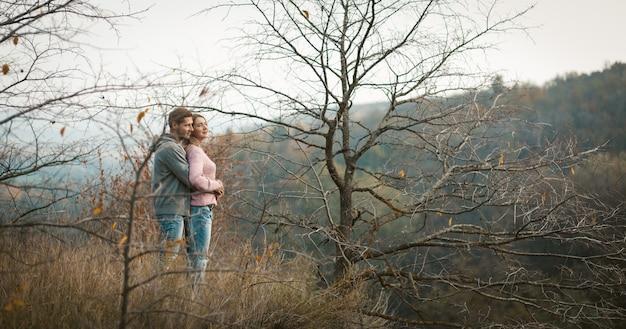 Abraçando o casal apaixonado fica na encosta de uma colina, olhando para baixo, jovem e uma mulher admiram a floresta de outono que cresce nas encostas abaixo