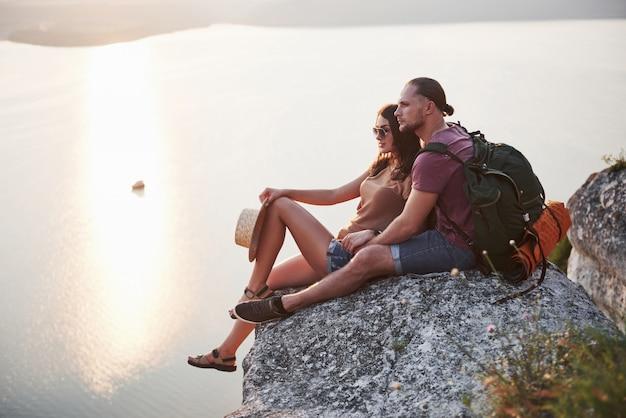 Abraçando o casal com mochila sentado no topo da montanha de pedra, apreciando a vista costeia um rio ou lago.