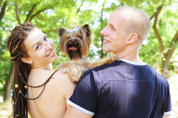 Abraçando o casal e seu yorkshire terrier, felizes no amor, ensolarado outono ao ar livre