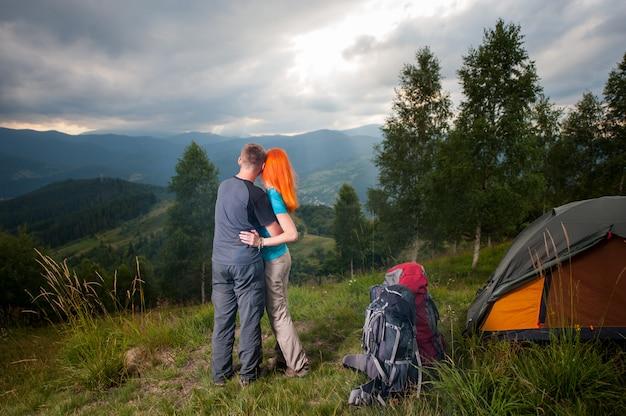 Abraçando o casal em pé de volta perto do acampamento e olhando para a distância nas montanhas, florestas e perfurando os raios do sol através de um céu nublado ao pôr do sol