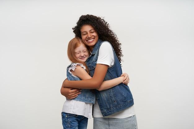 Abraçando o casal feliz de uma jovem morena de pele escura e uma adorável garota ruiva sorrindo amplamente e mantendo os olhos fechados, isolado no branco