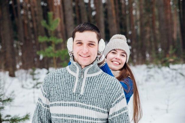 Abraçando o casal olhando com sorrisos em winter park