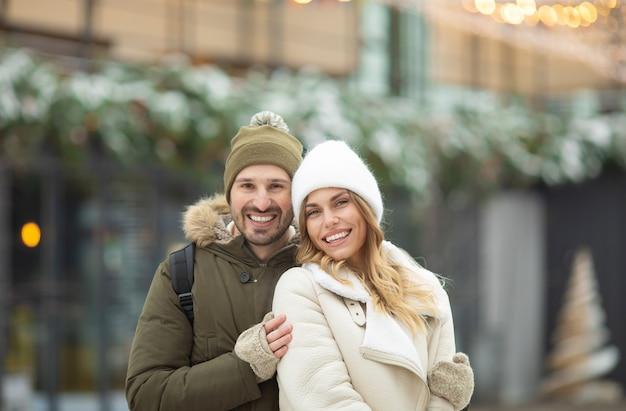 Abraçando o casal olhando para a câmera com sorrisos em winter park.