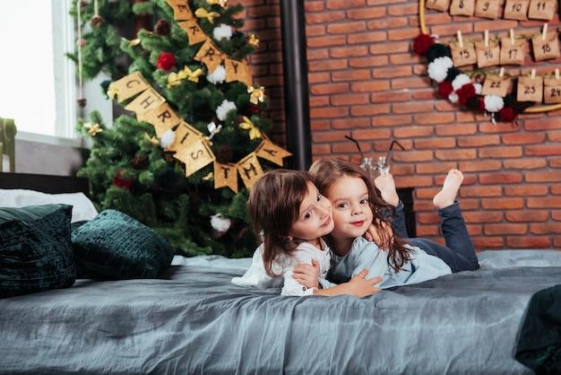 Abraçando-se. duas crianças alegres do sexo feminino, deitada na cama com decorações de ano novo e árvore do feriado.