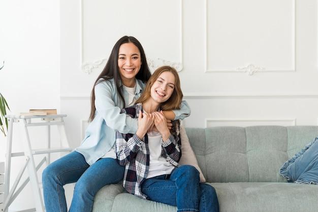 Abraçando senhoras sentada no sofá e sorrindo
