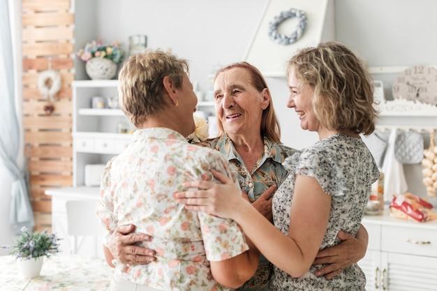 Abraçando sorrindo mulheres de geração multi em casa