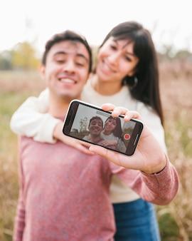 Abraçar, par jovem, levando, selfie, com, smartphone
