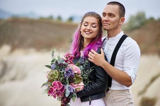 Abrace e beije um casal apaixonado em uma manhã de primavera na natureza. dia dos namorados, um relacionamento próximo entre um homem e uma mulher. homem beijando garota com cabelo colorido brilhante, coloração criativa
