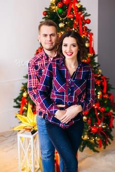 Abrace um casal apaixonado que olha para as lentes da câmera e sorri no espaço de uma árvore de natal