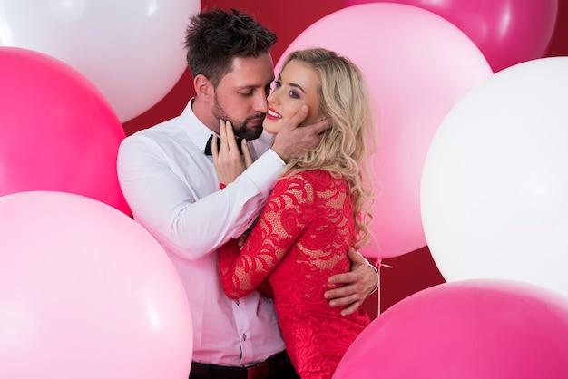 Abraço apaixonado entre os balões coloridos