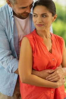 Abraço do marido. linda mulher de cabelos escuros se sentindo feliz enquanto o marido a abraça