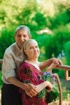 Abraço e beijo do casal de velhos em um parque em um dia ensolarado.