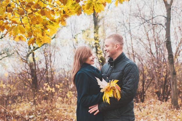 Abraços afetuosos e aconchegantes de um jovem casal apaixonado no parque de outono