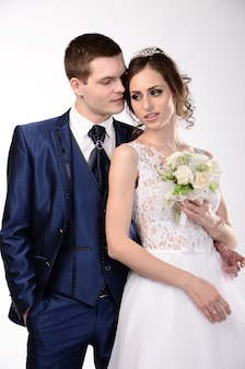 Abraços de casal apaixonado. noiva com cílios em um fundo branco.
