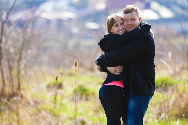 Abraços de casal sorridente fofo alegre. jovem de suéter abraça uma rapariga loira num dia quente de primavera. relacionamentos românticos de sucesso e o conceito de momentos felizes.