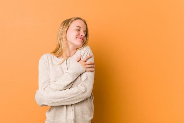 Abraços de mulher adolescente bonito e natural, sorrindo despreocupado e feliz.