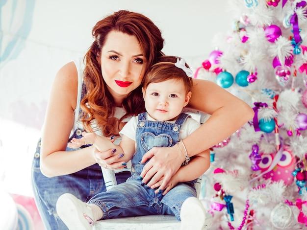 Abraços de mulher por trás, criança pequena sorrindo antes da árvore de natal