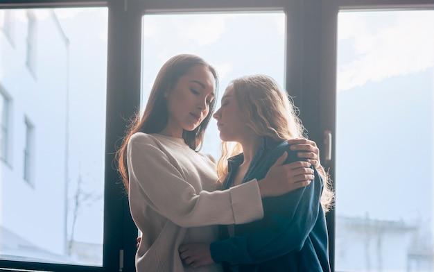 Abraços de namorados lésbicas multiétnicas em frente à janela