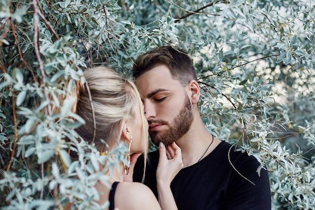 Abraços e beijos casal apaixonado nos galhos dos arbustos. ande pela estrada, um homem beijando uma mulher. amor, carinho, relacionamento, emoções vivas no rosto. casal amoroso oriental