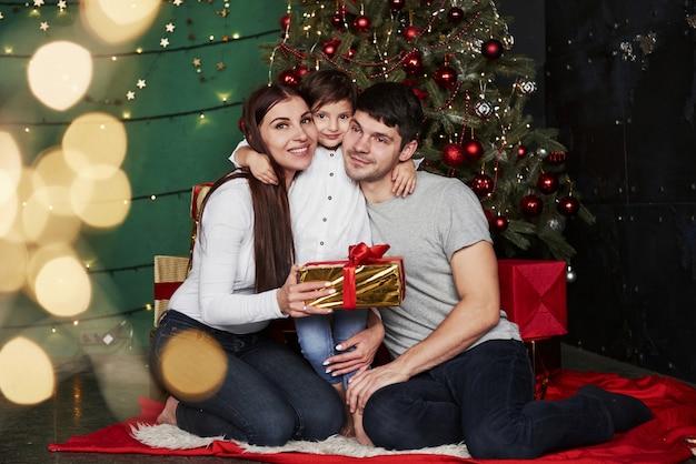 Abraços fofos. linda família senta-se perto da árvore de natal com caixas de presente na noite de inverno, aproveitando o tempo que passam juntos