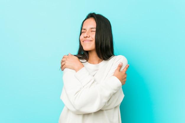 Abraços latino-americanos bonitos novos da mulher, sorrindo despreocupados e felizes.