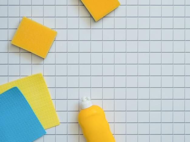 Abrigue produtos de limpeza no fundo branco do mosaico com espaço da cópia.