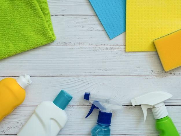 Abrigue produtos de limpeza no fundo de madeira branco com espaço da cópia.