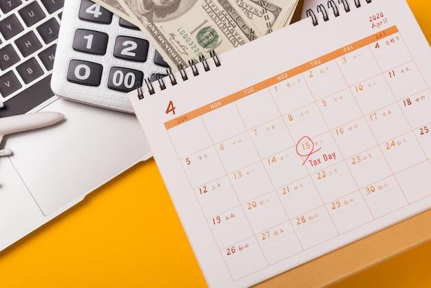 Abril do ano é o dia do imposto, calculadora closeup, computador portátil, calendário e conceito de orçamento financeiro do dólar dinheiro negócios