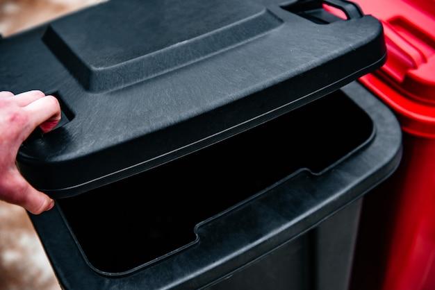 Abrindo a tampa da lata de lixo para jogar o lixo fora.