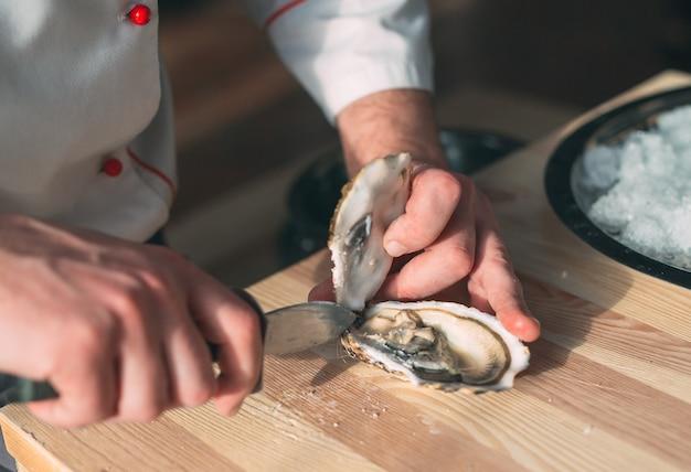 Abrindo as ostras ocas e planas. chef abre ostras no restaurante.