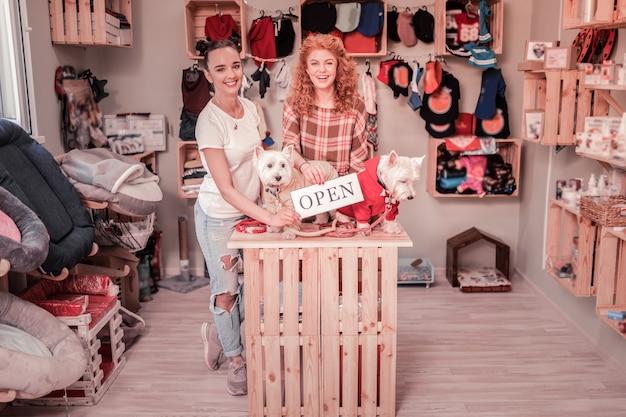 Abrindo loja própria. duas jovens bem-sucedidas se sentindo felizes ao abrir sua própria loja de animais de estimação