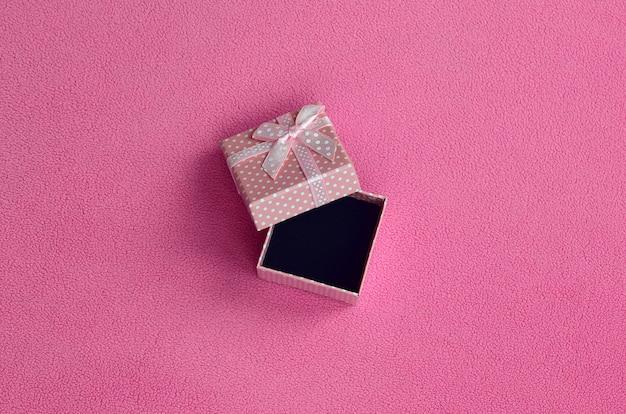 Abrir pequena caixa de presente em rosa com um pequeno arco encontra-se em um cobertor de tecido de lã rosa claro macio e peludo.