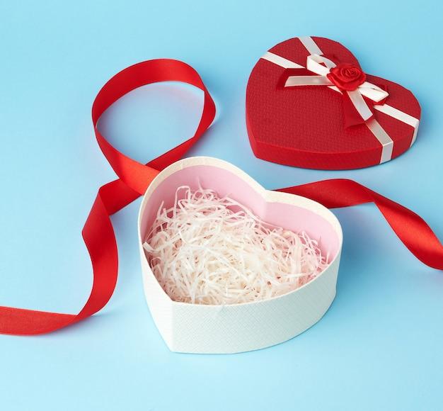 Abriu a caixa de presente em forma de coração vermelha com um laço em um fundo azul