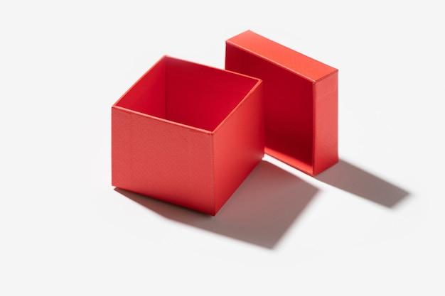 Abriu a caixinha de presente feita de papel vermelho, isolada no fundo branco