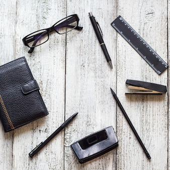 Abriu o bloco de notas em branco, cadernos, caneta, lápis, óculos, bolsa na mesa de madeira