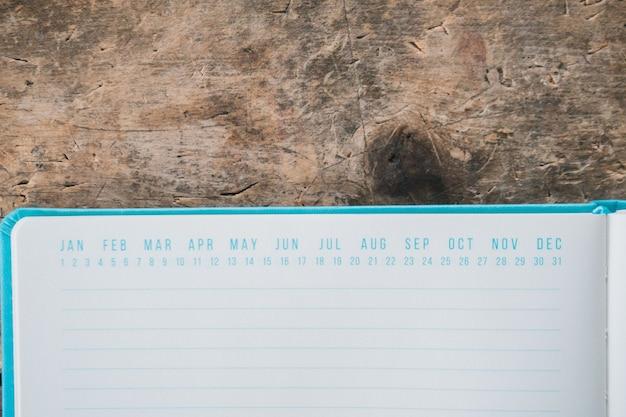 Abriu o livro azul com marcadores de data no topo em uma superfície de madeira