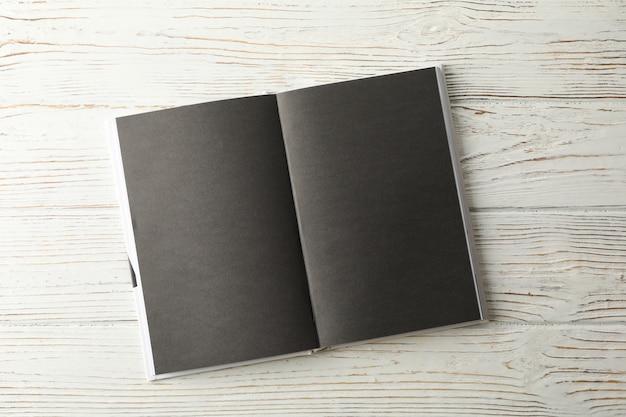Abriu o livro vazio com folhas pretas no espaço de madeira, espaço para texto