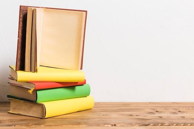 Abriu o livro vazio na pilha de livros coloridos na mesa de madeira