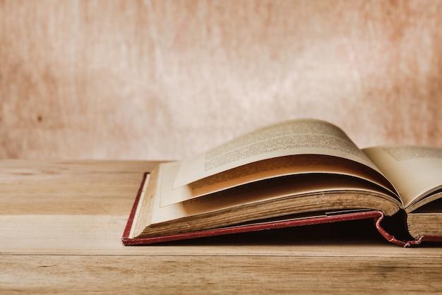 Abriu o livro velho na mesa de madeira