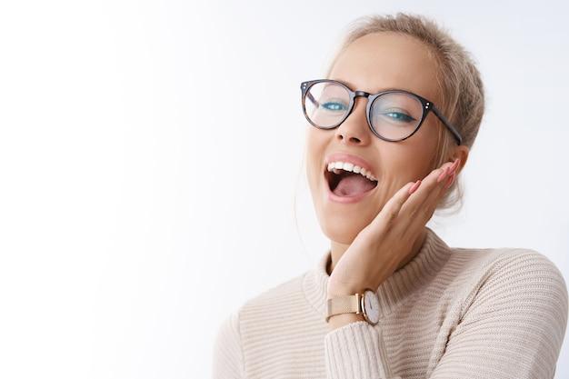 Absolutamente feliz. foto de estúdio de mulher divertida e animada, despreocupada e alegre, relaxando, se divertindo, cantando e sorrindo, tocando alegre, tocando a bochecha, levantando a cabeça, dançando contra um fundo branco