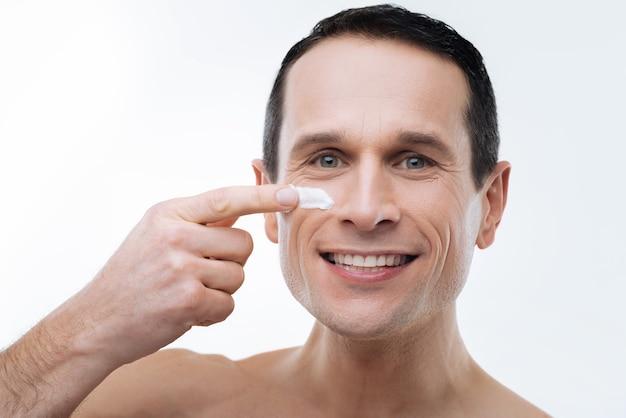 Absolutamente lindo. retrato de um homem feliz bonito e positivo sorrindo e olhando para você enquanto aplica o creme no rosto