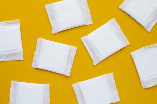 Absorventes higiênicos brancos na superfície amarela