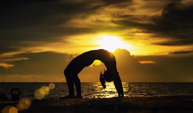 Abstrac. ioga de silhueta. retrato de jovem praticando ioga no mar. relaxar no mar. meditação