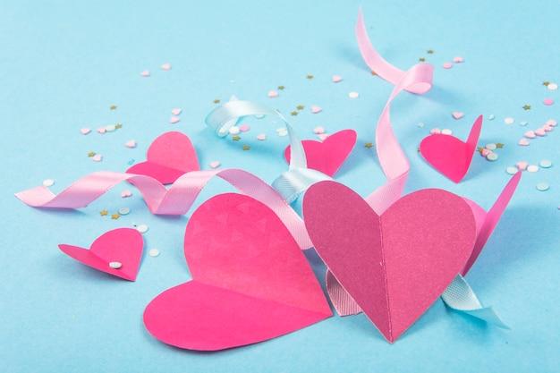 Abstrato com corações de papel, fitas para dia dos namorados.