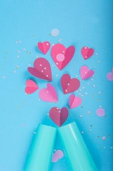 Abstrato com corações de papel, taça de champanhe azul para o dia dos namorados.
