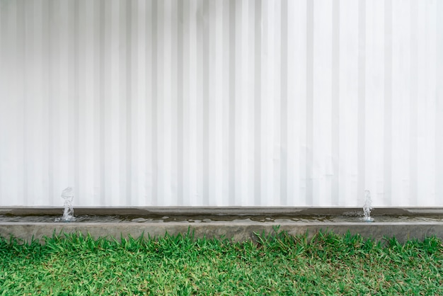 Abstrato da parede branca com grama verde em primeiro plano