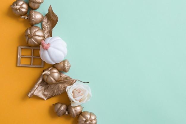 Abstrato de outono com abóboras douradas, folhas e bolotas em cenários de papel colorido com espaço de cópia