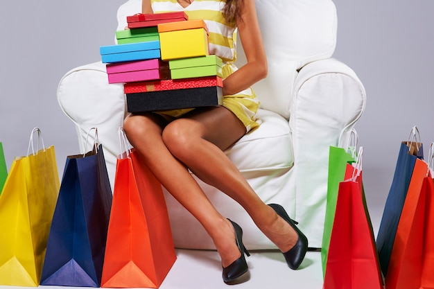 Abundância de sacolas de compras ao redor da mulher