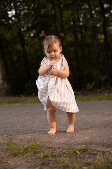 Aby garota se divertir no parque, correndo com os pés descalços na grama verde.