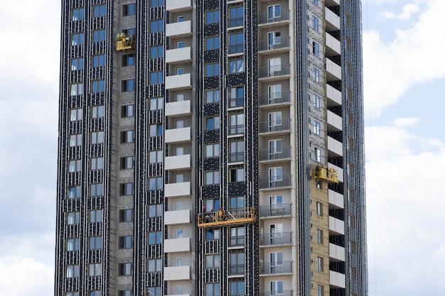 Acabamento de edifício residencial em construção com placas de isolamento térmico.